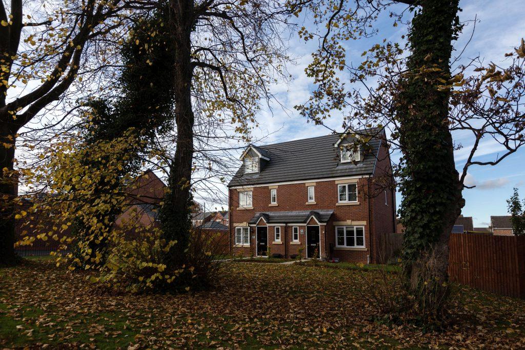 A semi detached house through some autumn trees